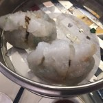 Two Chiu Chow Fun Gor dumplings in a metal steamer.
