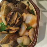 Clams with black bean sauce, served in a brown polygonal bowl.