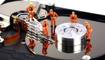 Miniature technicians work on hard drive. Image representing 'big data' but also 'little data'
