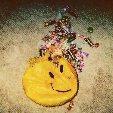 Smiley-faced pinata with candy spewing out of the top.