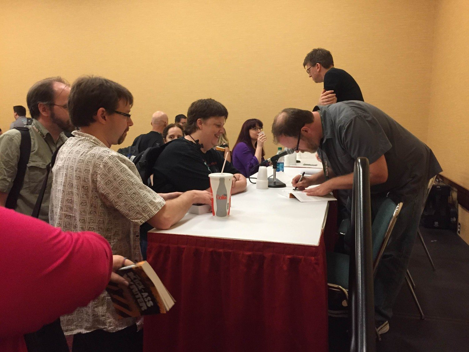 Chuck Wendig signs books for a fan after a panel