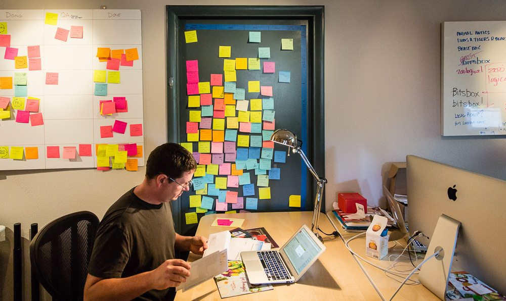 Scott Lininger sits at a desk, a white board and closed door to his side, covered in multicolored sticky notes with ideas written on them.
