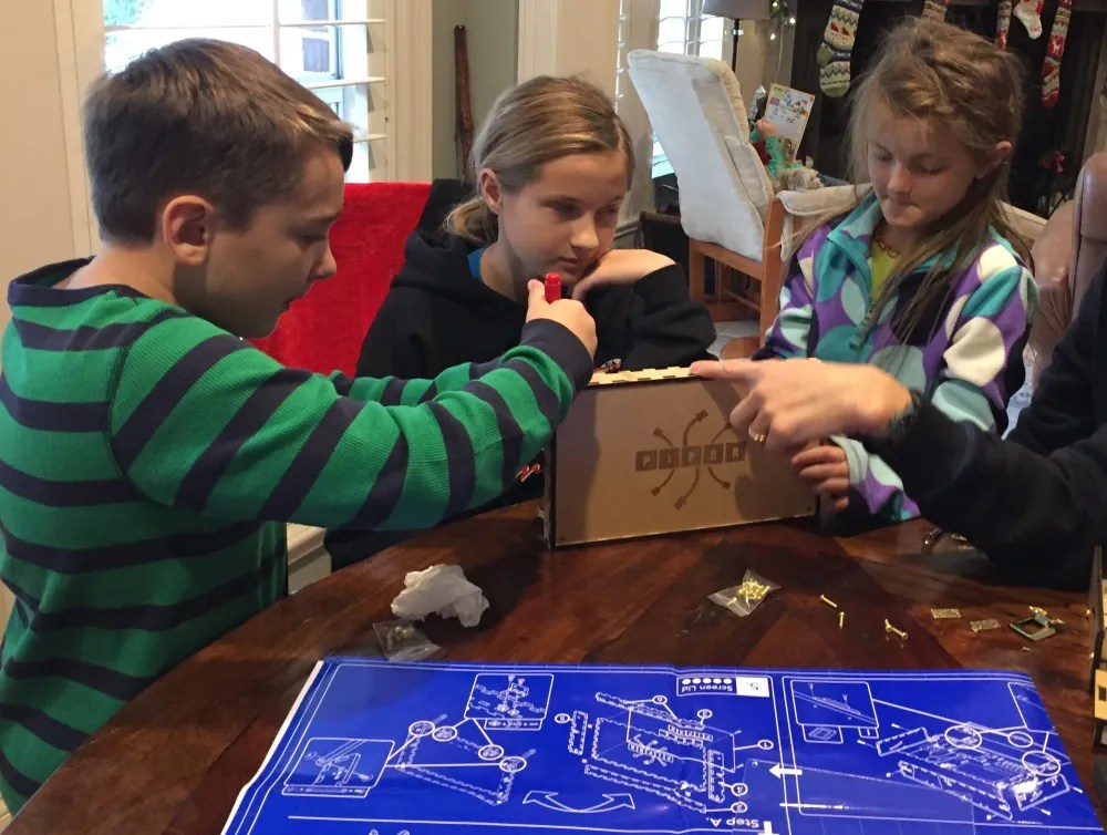 Three children work on a science fair project in a brown box on a table using a screwdriver, next to a large blue schematic.
