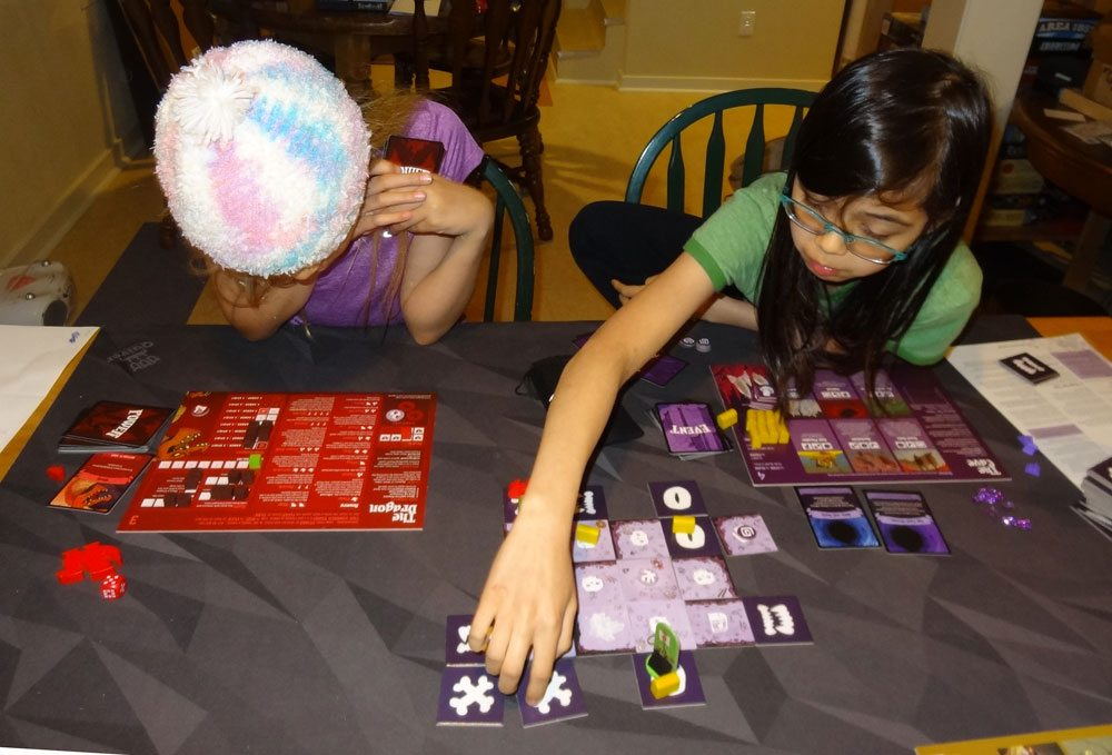 My 9-year-old studies her Dragon abilities, while the 12-year-old places some new Cave tiles. Photo: Jonathan H. Liu