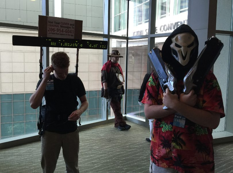 Overwatch cosplay from PAX West 2016. A reaper in a Hawaiian shirt is close to the camera at the front right, guns across his chest, with a McCree leaning up against a glass wall in the background. To the left is a non-cosplay person with a LED display mounted on his back advertising for people to send him their original text message, which will be displayed on the LED board.