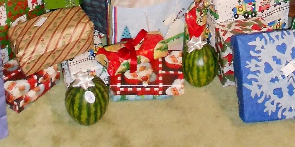 """two """"baby"""" watermelon with bows sitting among other wrapped gifts"""