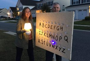 The author holding a board with fabric wallpaper and lights, with a letter painted beside each light from A to Z. A woman dressed as Joyce from Stranger Things is to the left.