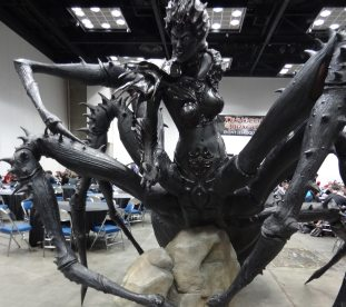 Welcome to Gen Con! Lolth, Demon Queen of Spiders, greets gamers at the Wizards of the Coast area in the gaming hall.