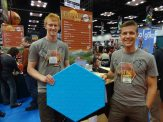 Nate Veldkamp and Bill Trammel proudly display their Catan Board—they're now taking preorders for more boards, and people were signing up for them.