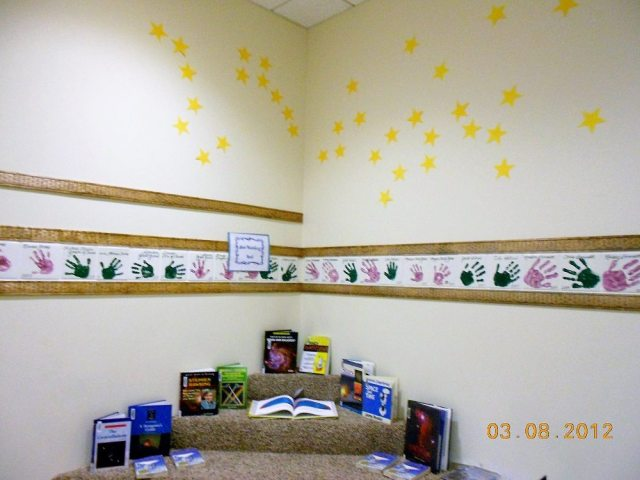 Carpeted risers with astrophysics books, construction paper stars in constellation patterns on the wall above it
