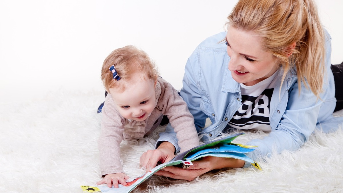 Woman holding a book open for a baby, who is diving at it excitedly