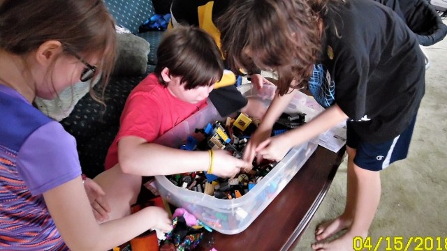 Children bending over a large bin of Lego on a coffee table, sorting through looking for pennies.