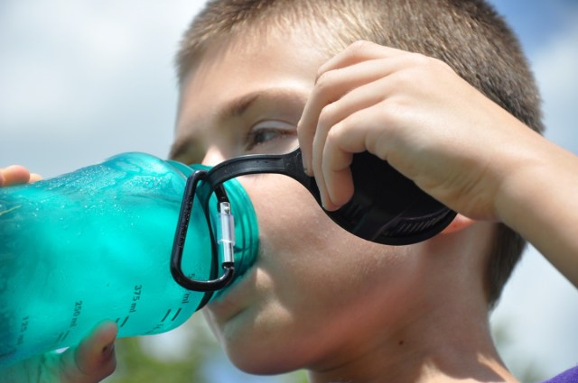 A white child drinks from a blue water bottle