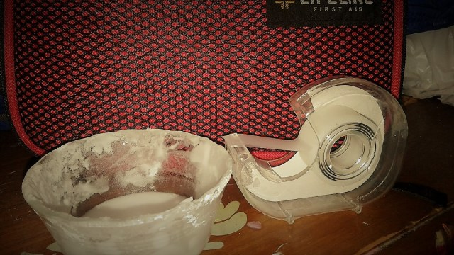 a dish of white goop (baking soda paste) and a roll of scotch tape in front of a first aid kit