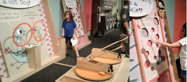 """Two catapults facing movable hoops being cranked by 11yo, in front of Pigeon and Duckling picture; board with holes with a pulley device for lifting """"cookies"""" to holes for the Pigeon or Duckling"""
