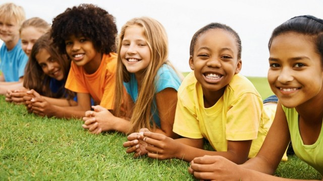 A line of smiling children of various ethnicities