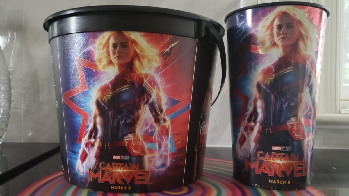 Captain Marvel movie images on a popcorn bucket and soda cup