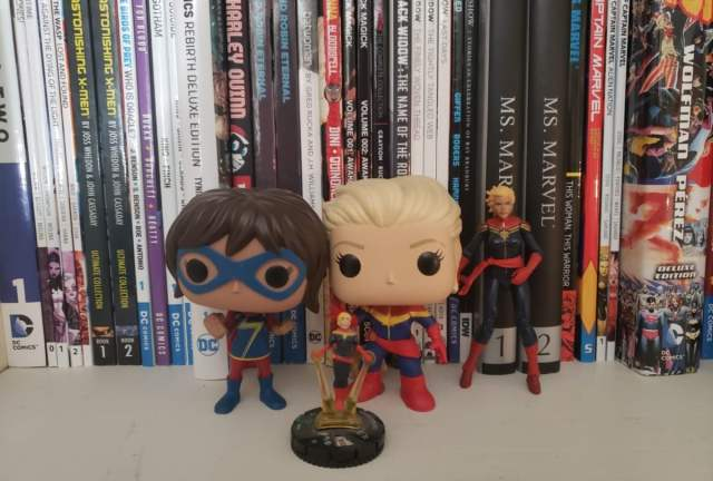 Figures of Kamala Khan and Carol Danvers as Captain Marvel set against a shelf of comic books.