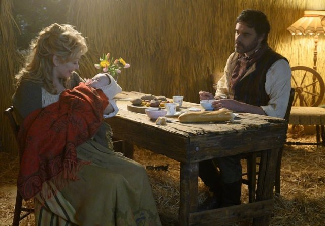 Jean Smart as Melanie Bird as a fairy-tale peasant wife, rocking a baby, and Jemaine Clements as Oliver Bird as a fairy-tale peasant husband