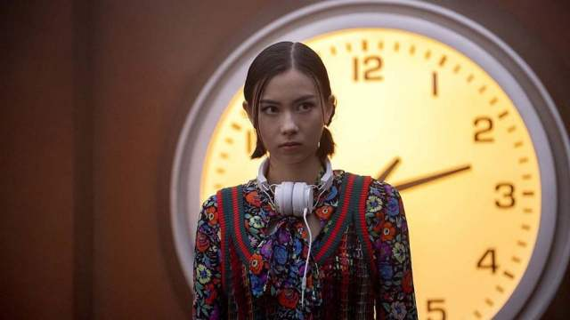 Lauren Tsai as Switch, looking incredulous in front of a big clock