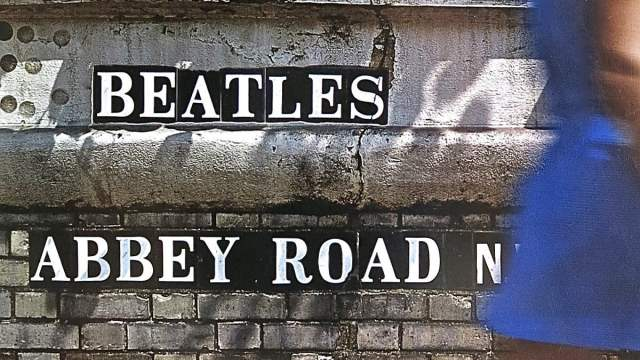 widescreen crop of the back cover of the Beatles' 'Abbey Road' album which shows the letters of artist and title embedded in a stone wall as a woman walks past