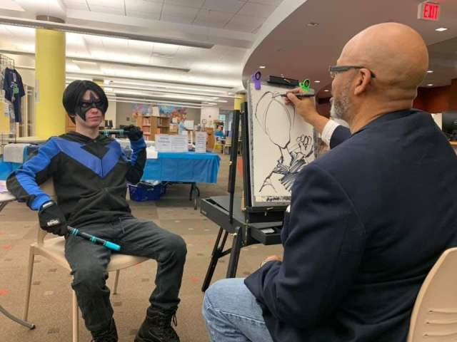 Caricaturist draws a cosplayer dressed as Nightwing