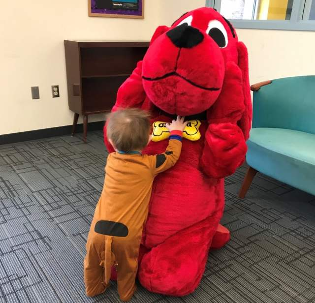 toddler dressed as Scooby-Doo dives at person dressed as Clifford, who is leaning away in exaggerated shock