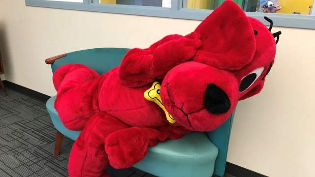 Person in a stuffed Clifford suit sprawls on a small loveseat, one ear over an eye