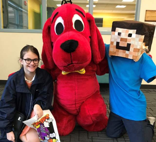 Person in Clifford costume poses with preteens dressed as Eleven from Stranger Things and Steve from Minecraft