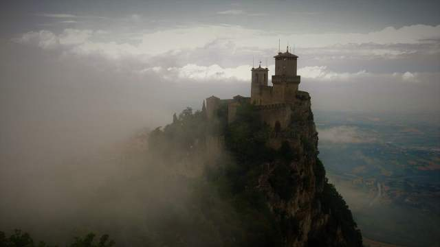 castle on a mountain surrounded by cloud