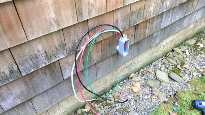 Wires sticking out from partly-installed exterior generator wiring conduit