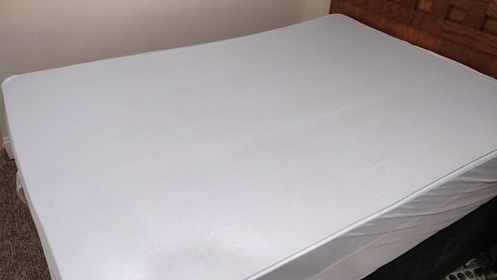 Mattress cover fully installed over the mattress and topper