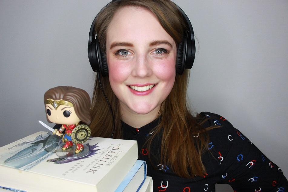 Ein Mensch mit Kopfhörern, einem Stapel Bücher und einer Funko-Pop-Figur von Wonder Woman. Foto: Lilli/geek's Antiques