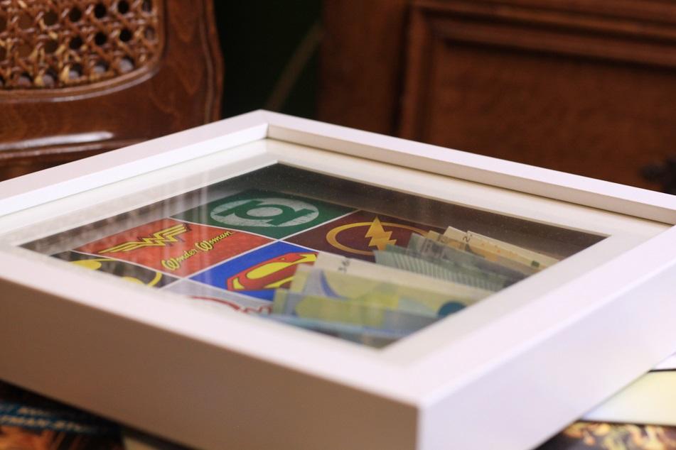 Bilderrahmen mit Comicmotiven und Geldscheinen. Foto: Lilli/geek's Antiques