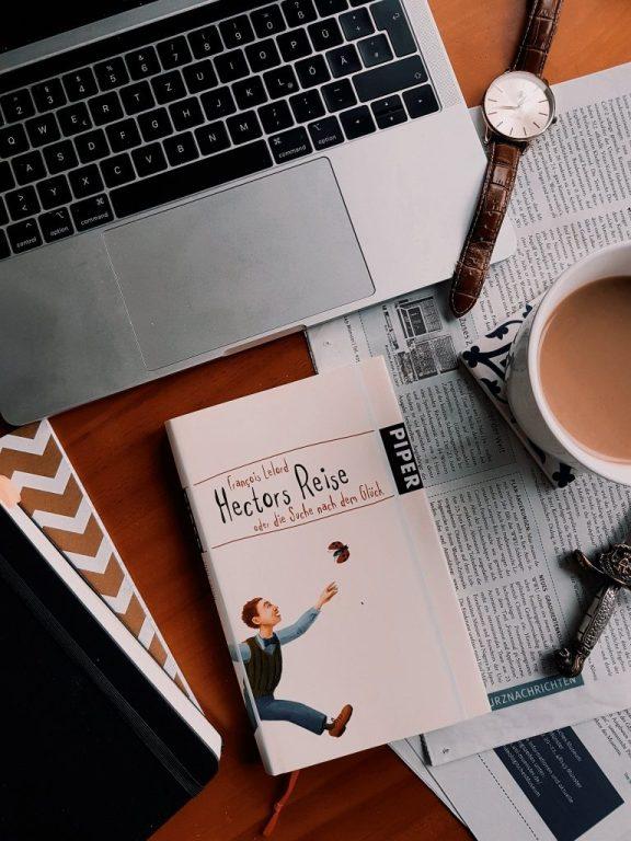 Ein Buch auf einem Tisch mit Zeitung, Kaffee und Notizbüchern. Foto: Lilli/geek's Antiques
