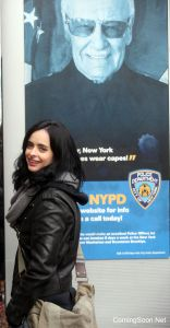 """NEW YORK, NY - DECEMBER 07: Krysten Ritter as """"Jessica Jones"""" stands in front of a prop poster of Stan Lee filming Marvel's """"The Defenders"""" on December 7, 2016 in New York City. (Photo by Steve Sands/GC Images)"""
