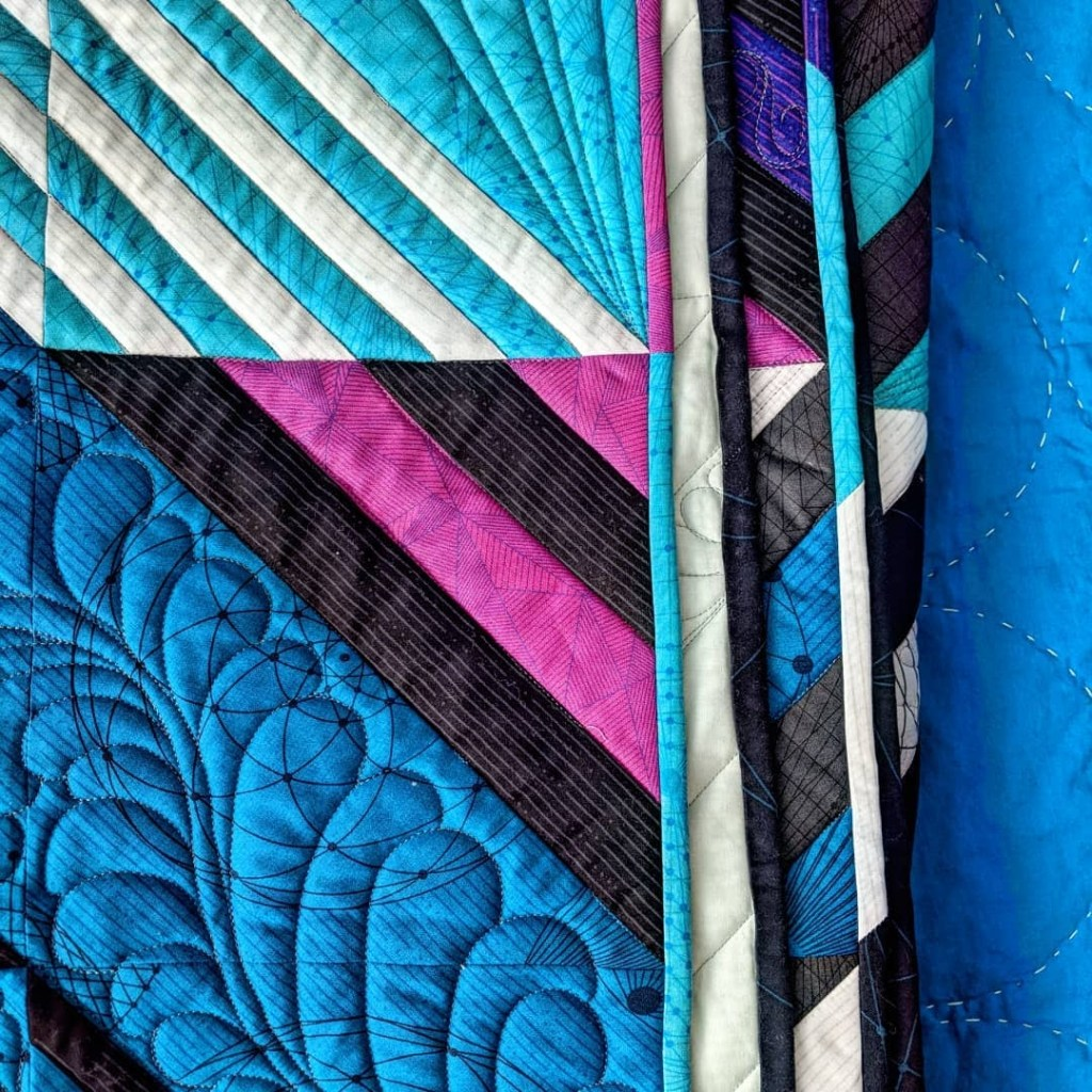 colorful scrappy binding on the Glitch quilt by Geeky Bobbin