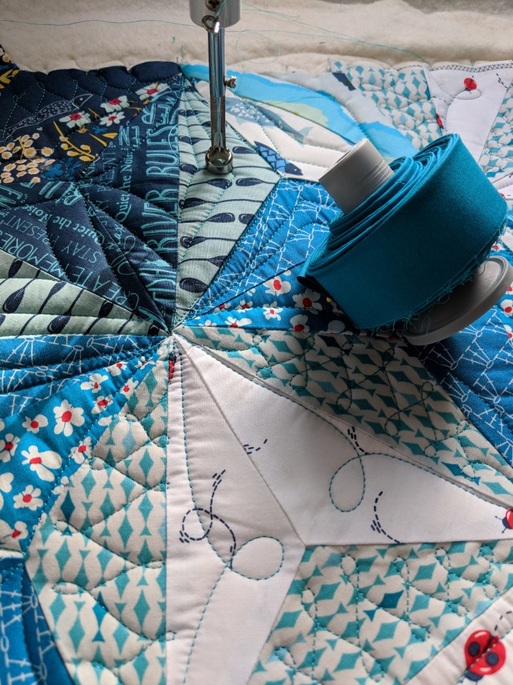 roll of binding about to be attached on a longarm. Intersectional quilt by geeky bobbin. fabrics by Mister Domestic.