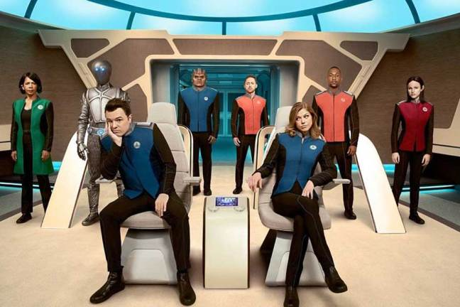 Picture of the crew on the bridge of a spaceship. Seth McFarlane sits in the captain chair, smirking