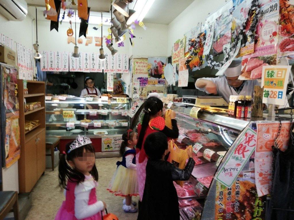 新町商店街のハロウィンでお肉屋さんからお菓子をもらう子供たち
