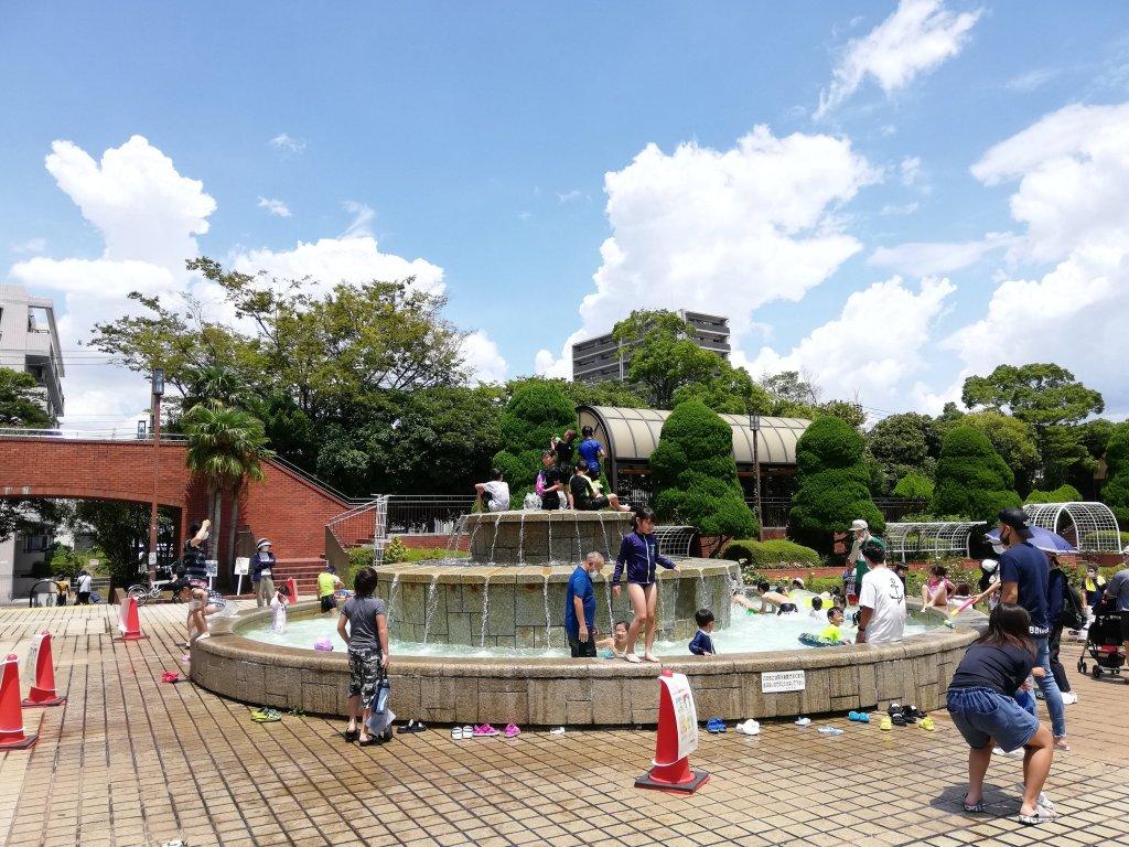 夏のフラワーガーデンの噴水で水遊びをする子供たち