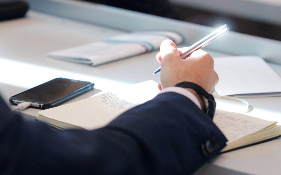 Das Bild zeigt einen Arm mit einem Stift in der Hand sowie einen Anzug und einen Tisch mit einem Handy darauf.
