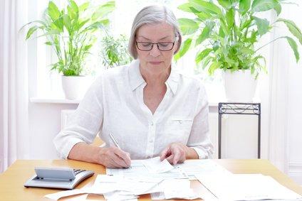 Grundfreibetrag Deutsche Seniorin füllt die Formulare für die jährliche Steuererklärung aus, im Wohnzimmer an einem Tisch mit Taschenrechner und vielen Rechnungen und Quittungen