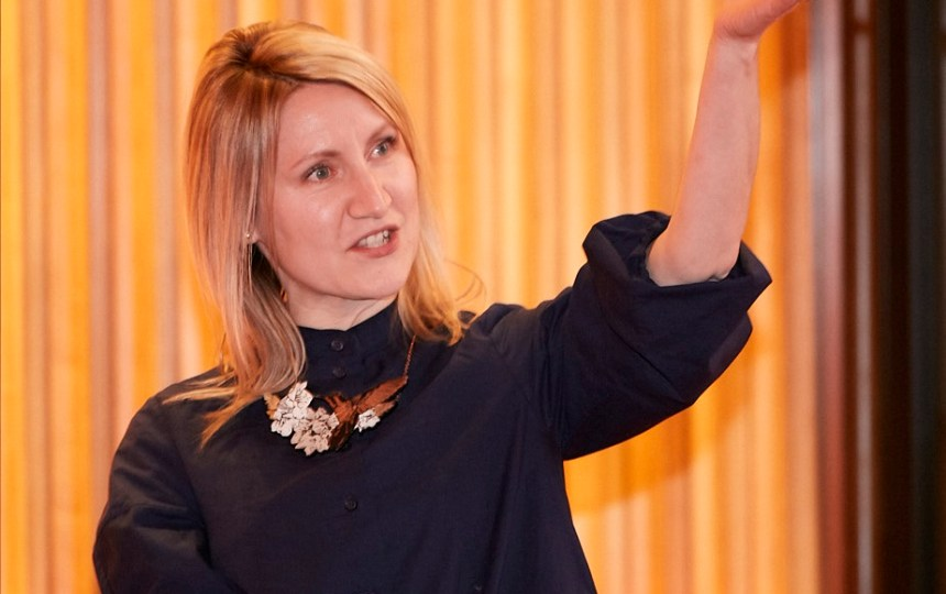 A woman presenting a talk with her hand raised in the air.