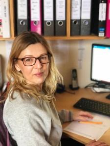 Sara Wallington sitting at a desk smiling at the camera