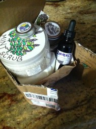 a colorful package from Good 4 You Herbals with mint scrub, cleavers tincture, yarrow balm, and apricot shimmer salve!