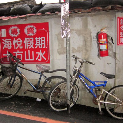 bikes against a wall with a fire extinguisher and chinese signs