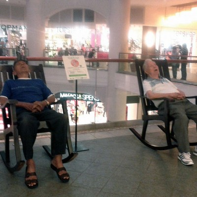 two men napping on rocking chairs in a mall