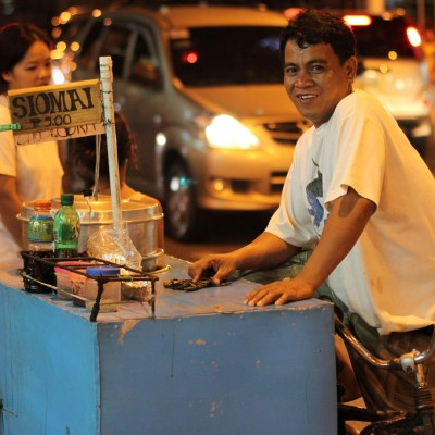 street vendor with bicycle cart at night
