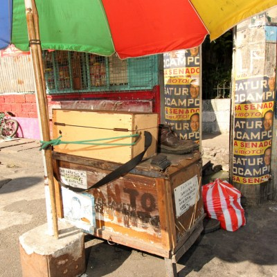 wooden shoe repairman's cart in front of posts with politicians' ads